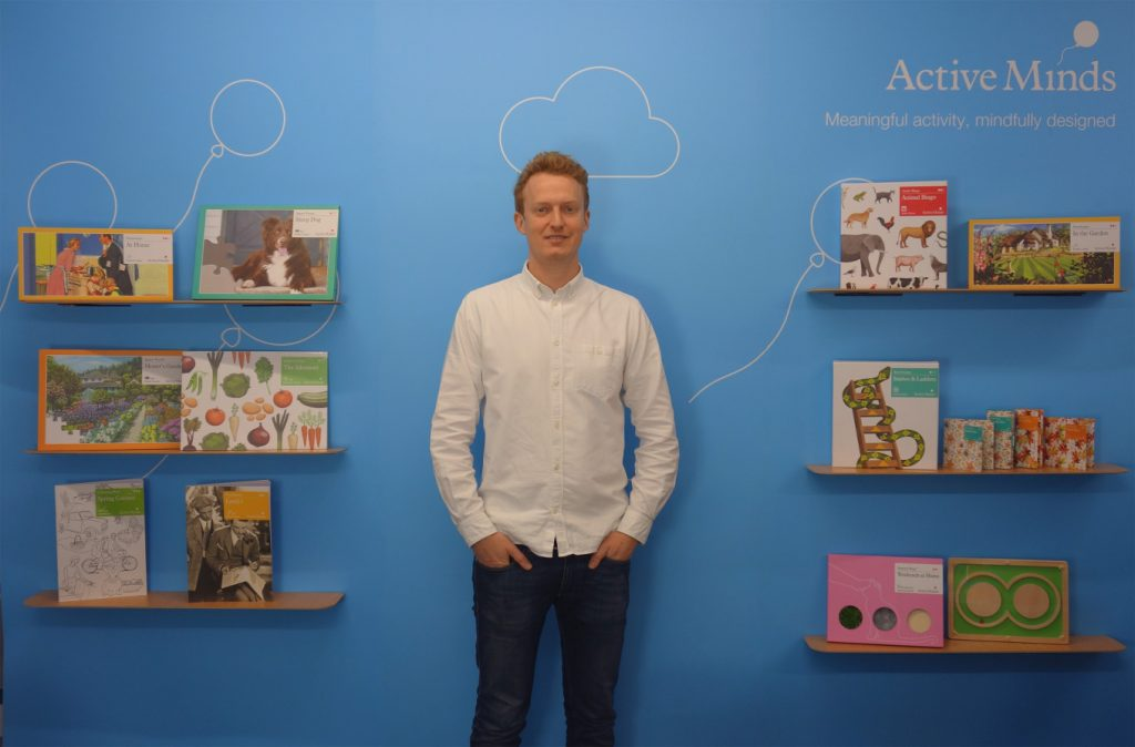 Active Minds founder Ben in front of shelves with their products.