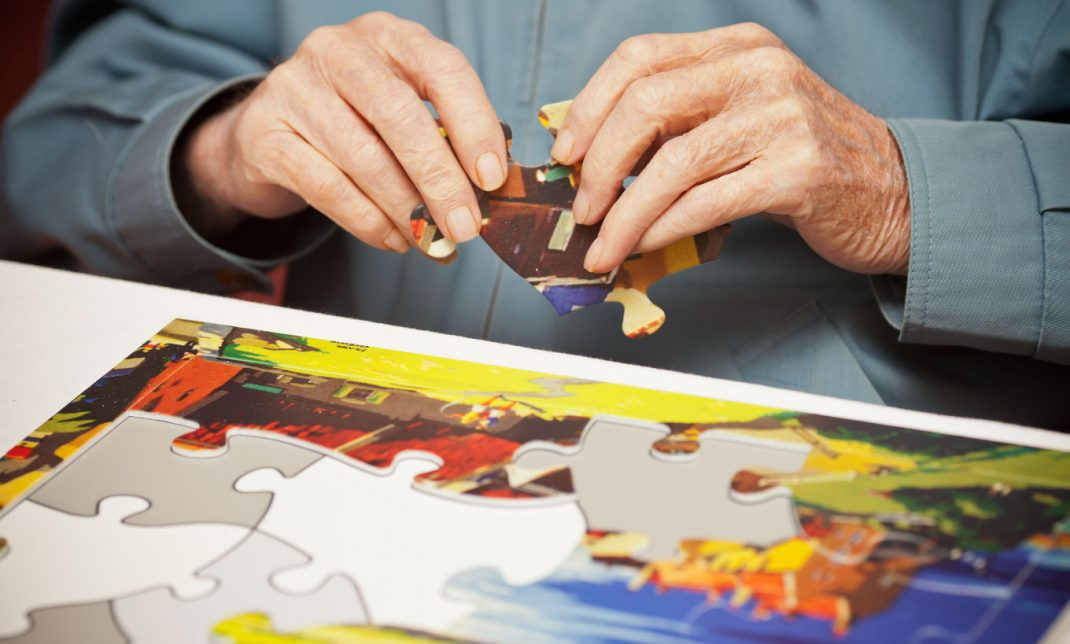 Hands making a special jigsaw puzzle designed for people living with dementia