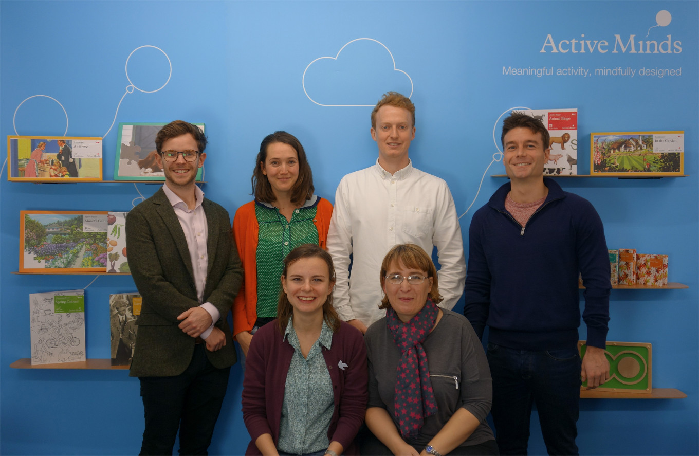 Active Minds' team in front of shelves with their product for people living with dementia